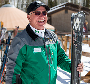 a ski valet smiling holding a set of skis
