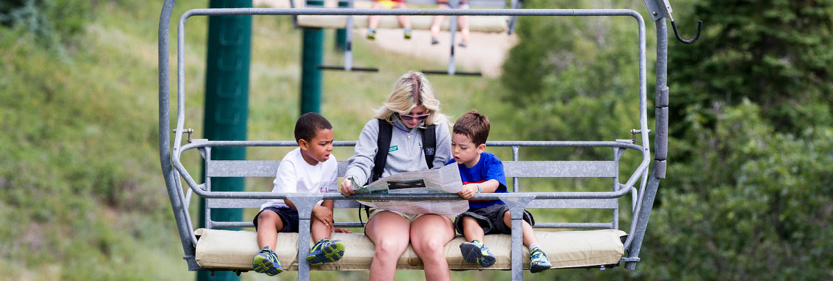 A summer adventure camp counselor reading a trail map with two kids on a chairlift