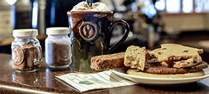 A coffee drink, biscotti, cookie and cinnamon and nutmeg shakers grouped together at the counter of deer valley etc.