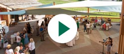 An event taking place on the Silver Lake Lodges deck during summer with a play button on the image to indicate video