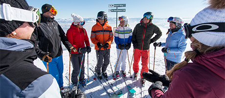 Group of skiers standing in a circle talking and smiling