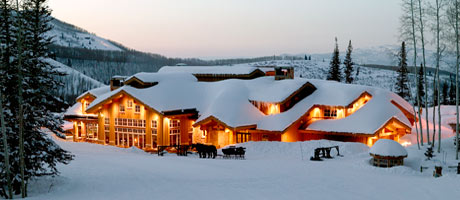 Exterior view of Empire Canyon Lodge and a horse-drawn sleigh on a winter evening