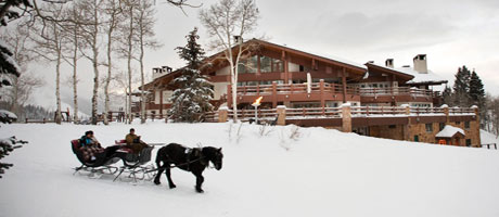 Exterior image of Stein Eriksen Lodge at dusk with horse drawn sleigh in the foreground