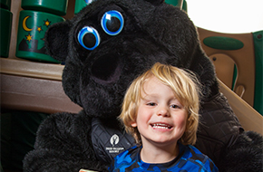 Child playing with Quincy the Bear mascot
