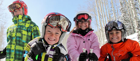 Group of four children smiling while skiing