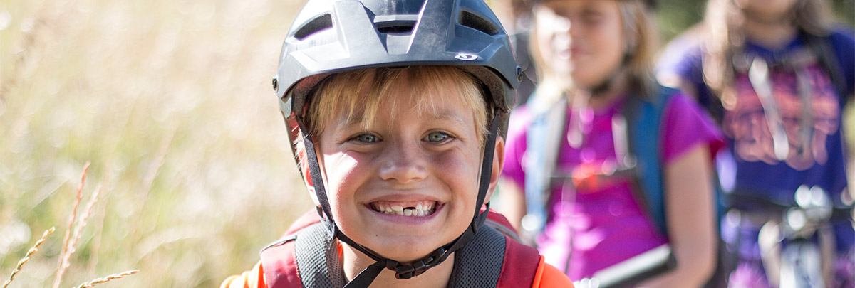 a little boy with a bike helmet on smiling