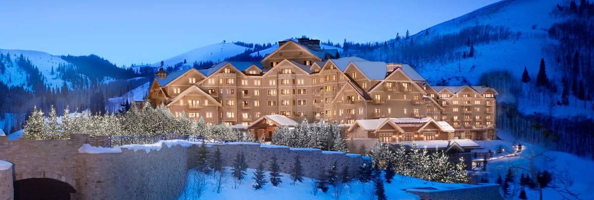 Exterior winter view of Montage Deer Valley at dusk with twinkling lights on the surrounding trees