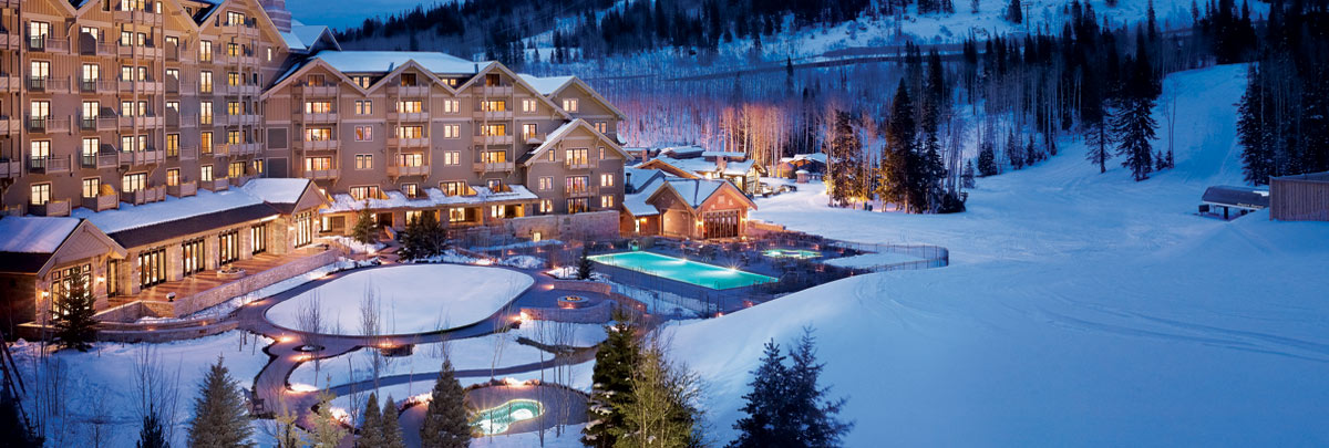 Exterior winter view of Montage Deer Valley with view of the outdoor pool at dusk