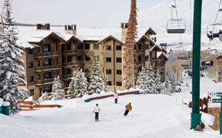 Exterior winter view of Arrowleaf condominiums with skiers and chairlift