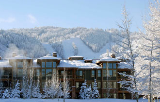 Exterior winter view of Lodges at Deer Valley with Deer Valley ski slopes in background