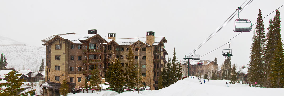 Exterior winter view of Arrowleaf condominiums with snow falling and ski lift in background