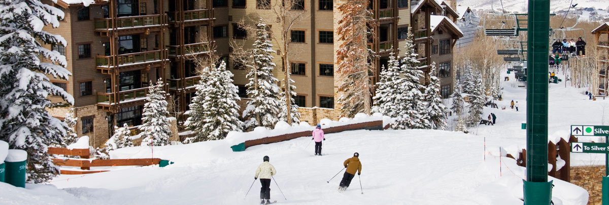 Exterior winter view of Arrowleaf condominiums with skiers