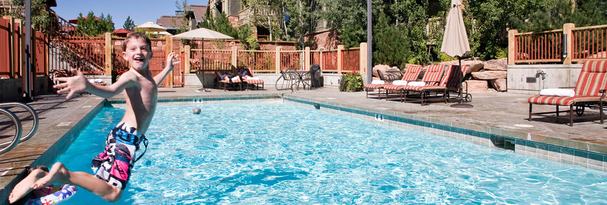 Exterior summer view of boy jumping into the swimming pool at Lodges at Deer Valley