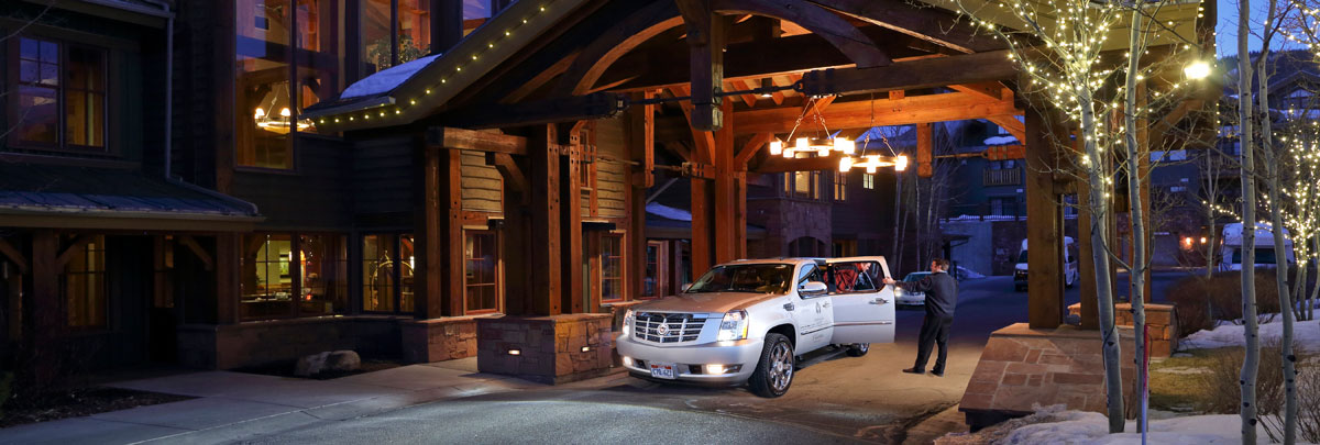 Exterior view of Lodges at Deer Valley and bellman helping a guest out of Deer Valley's transportation