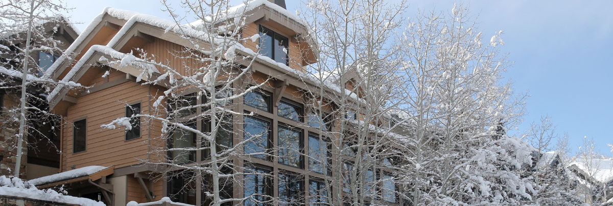 Exterior winter view of Portico with snow covered Aspen trees and blue skis