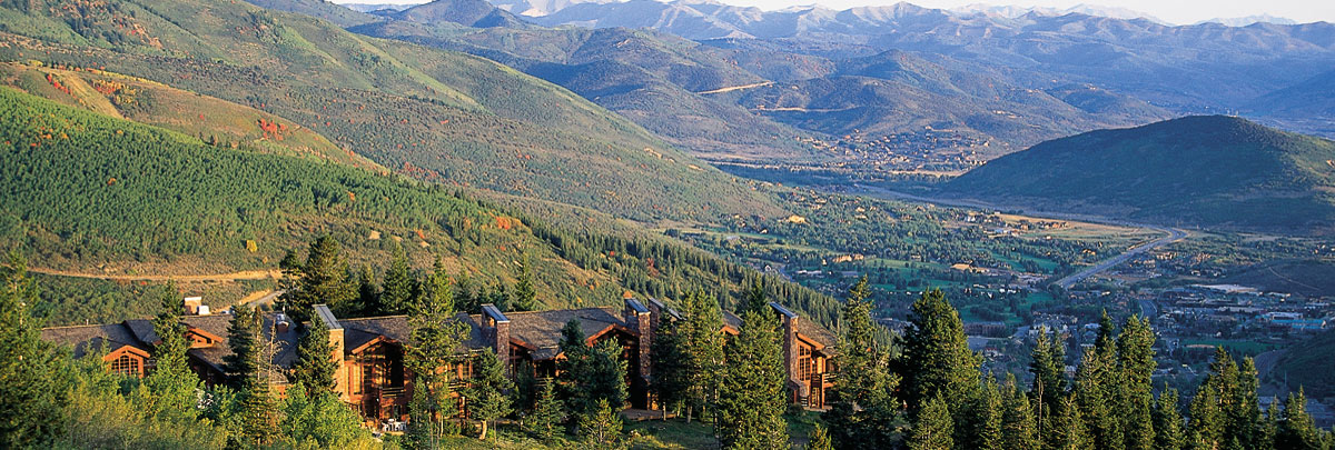 Exterior summer aerial view of Stag Lodge and views of the Wasatch Mountains and Park City in the background