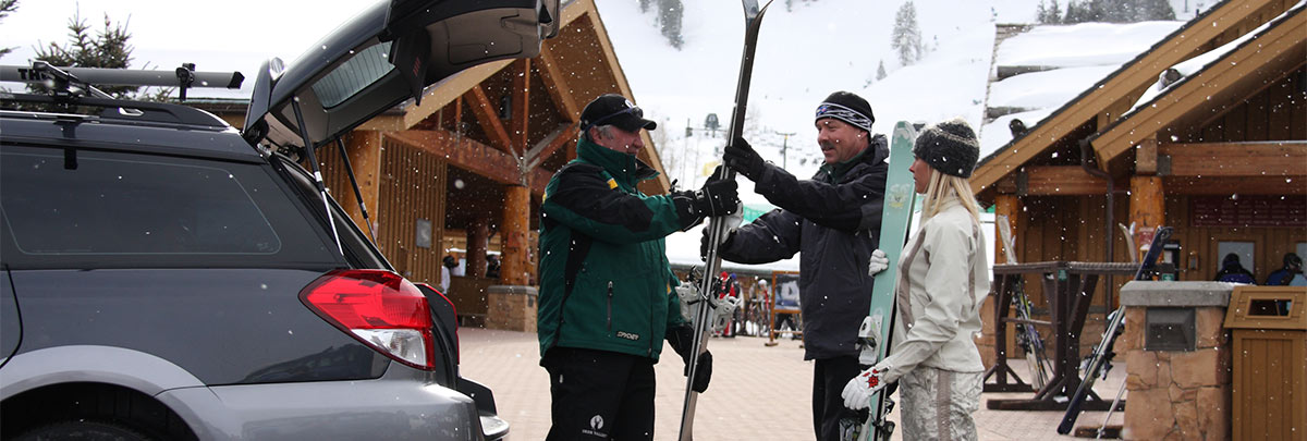 A ski valet helping a guest get their skis out of their car