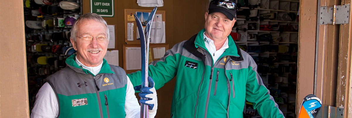 Two guest service staff smiling at ski storage