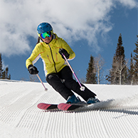 Skier in yellow jacket skiing a groomed ski run