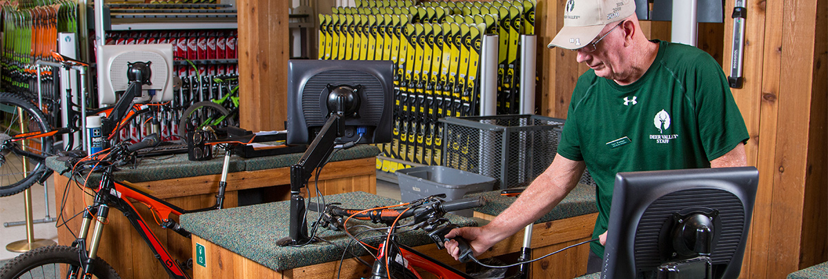 A bike rental associate scanning an orange scott mountain bike to be used as a rental