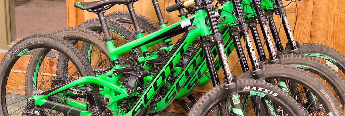 four green scott mountain bikes leaning against a wall