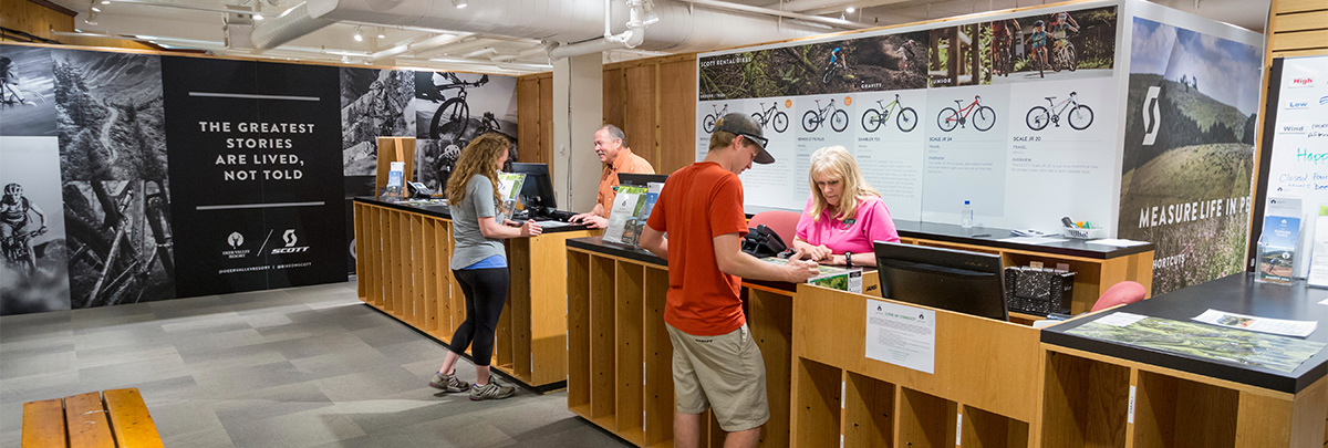 a male and female purchasing bike rentals at the counter in the rental office