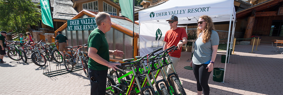 A bike rental associate showing a male and female the different types of mountain bikes they can rent outside