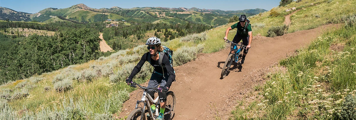 male mountain bike coach following a female mountain biker down a trail with mountains and ski runs in the background
