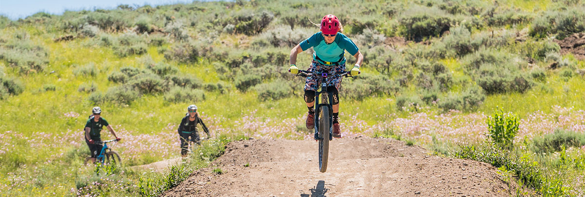 a female mountain biker going over a jump with another mountain biker and bike coach behind her