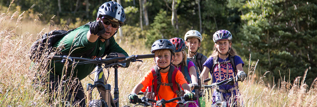 a male bike coach point out something to four kids on mountain bikes