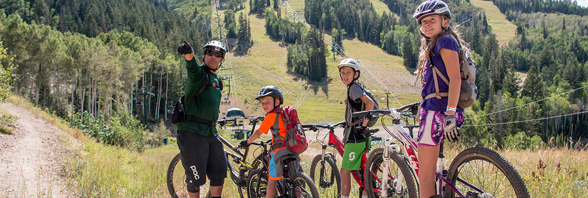 a male bike coach point up at something to three children mountain biker with ski hills and chairlifts in the background