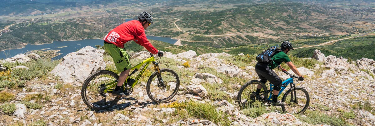 a bike coach leading a male mountain biker over large rocks with the jordanelle resevoir in the background