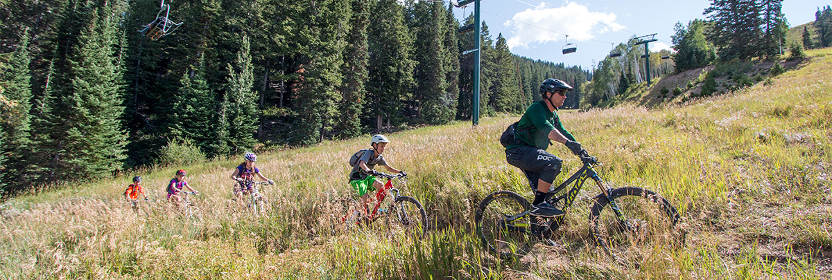 a male bike coach leading four kids on a trail with a chairlift in the background