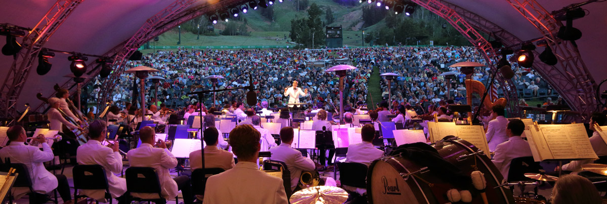 Image looking out from the snow park outdoor ampitheater with the utah symphony on stage looking out to the audience