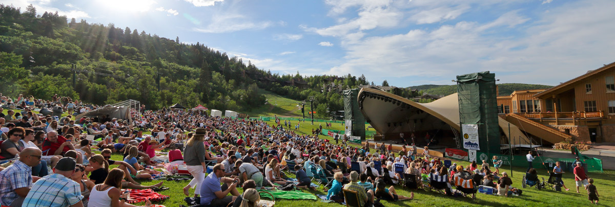 A large audience sitting on blankets and chairs in front of the snow park outdoor ampitheater listening to music on a sunny day