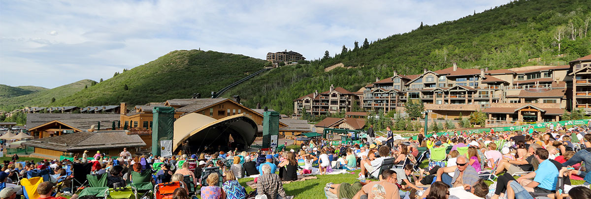 Snow Park Outdoor Ampitheater during the day with an audience on blankets and chairs with Black Diamond Lodge and St. Regis in the background