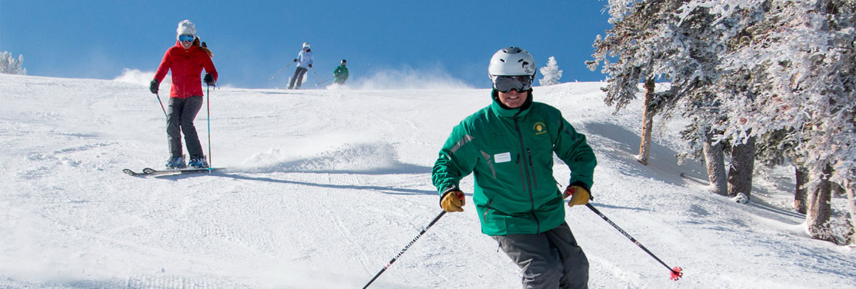 A Mountain Host skiing with guests on a tour