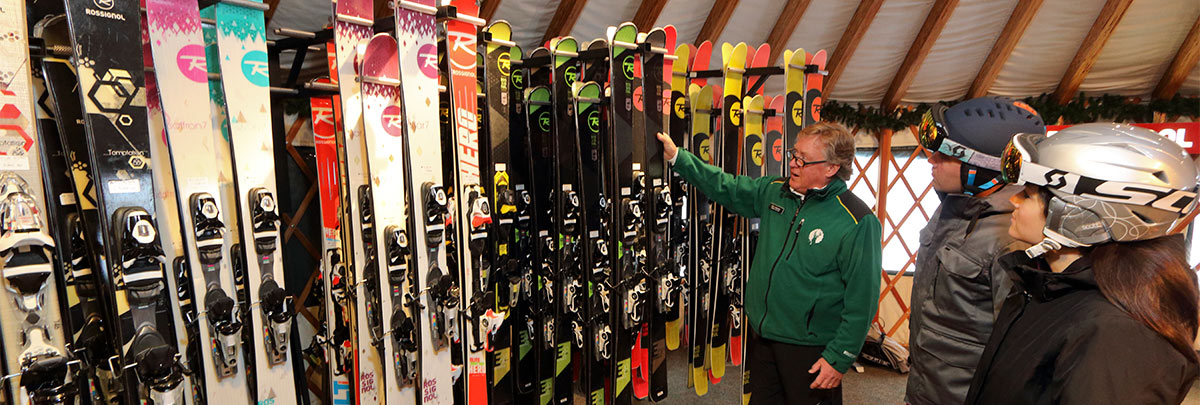 A Rossignol Yurt Associate showing different skis to two guests