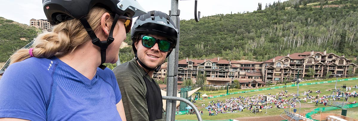 Two mountain bikers riding up a chairlift during Twilight Ride with a concert at Snow Park Outdoor Ampitheater in the background