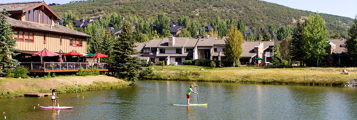 Two people stand up paddle boarding on the Deer Valley pond