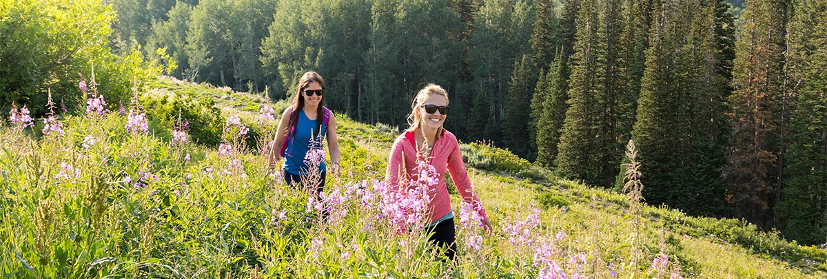 Two girls hiking and smiling through tall green grass and pink wildflowers