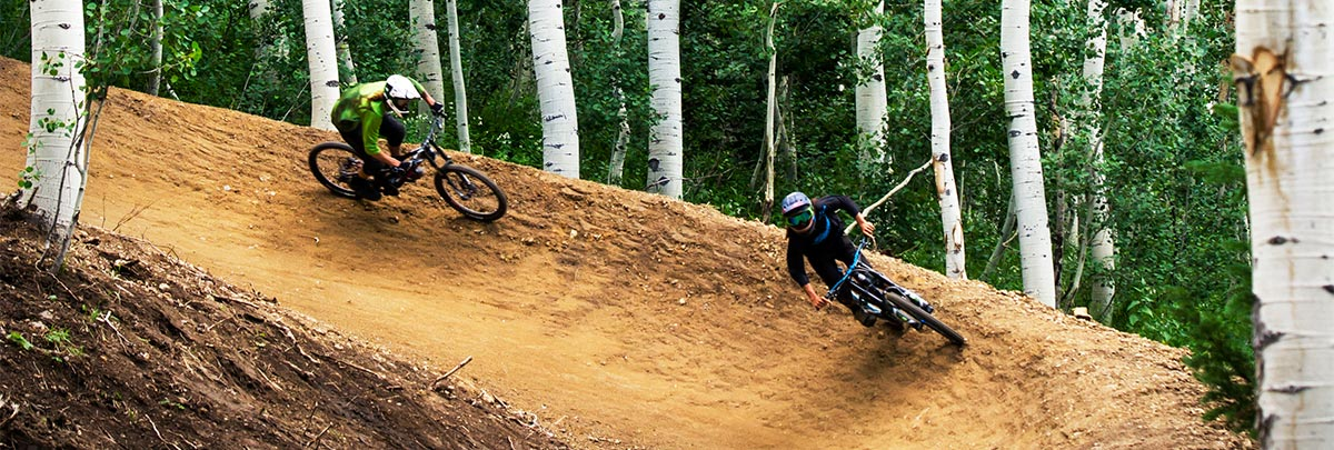 Two downhill mountain bikers riding on a flow trail through aspens