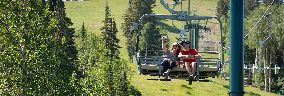 Two people taking a scenic chairlift riding and taking a selfie