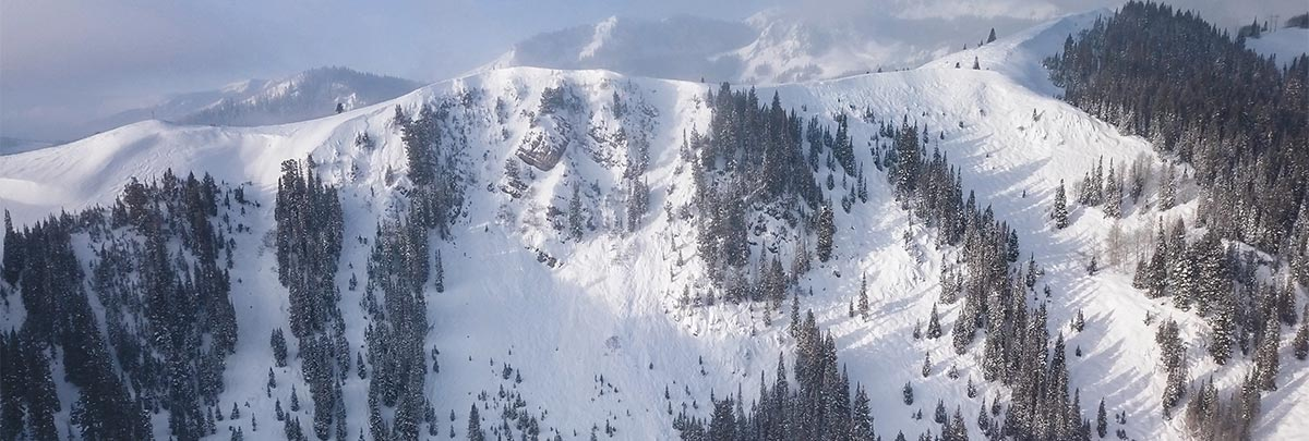 A person skiing with the Daly Chutes in the background