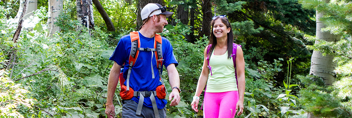 a young couple taking a hike together through the woods smiling