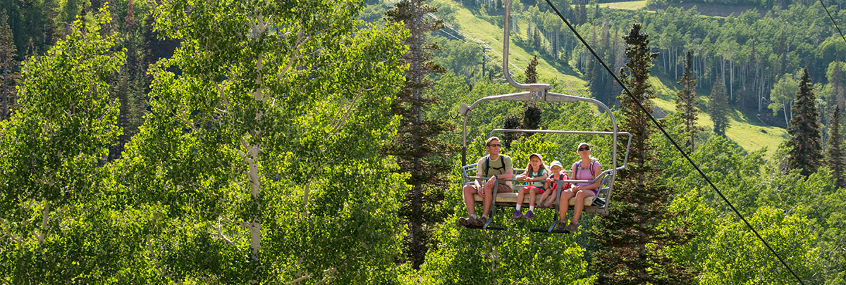 a family of four riding up a chairlift with green aspen trees in the background