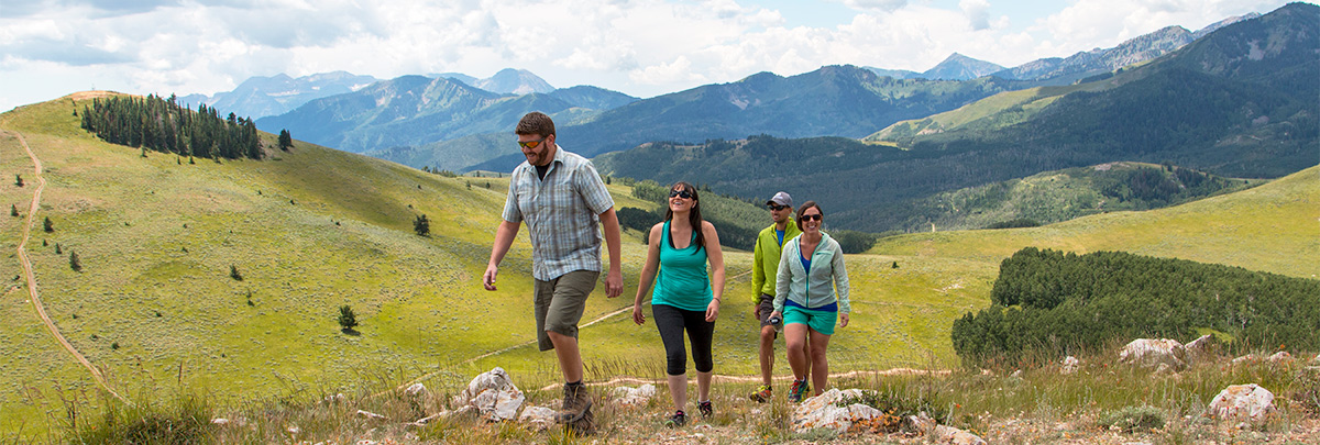 a group of four adults hiking up the backside of bald mountain with mountains in the background