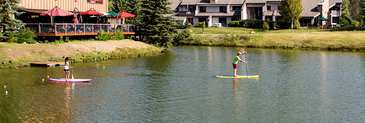 a male and female standup paddleboarding on the ponds with the deer valley grocery cafe deck in the background