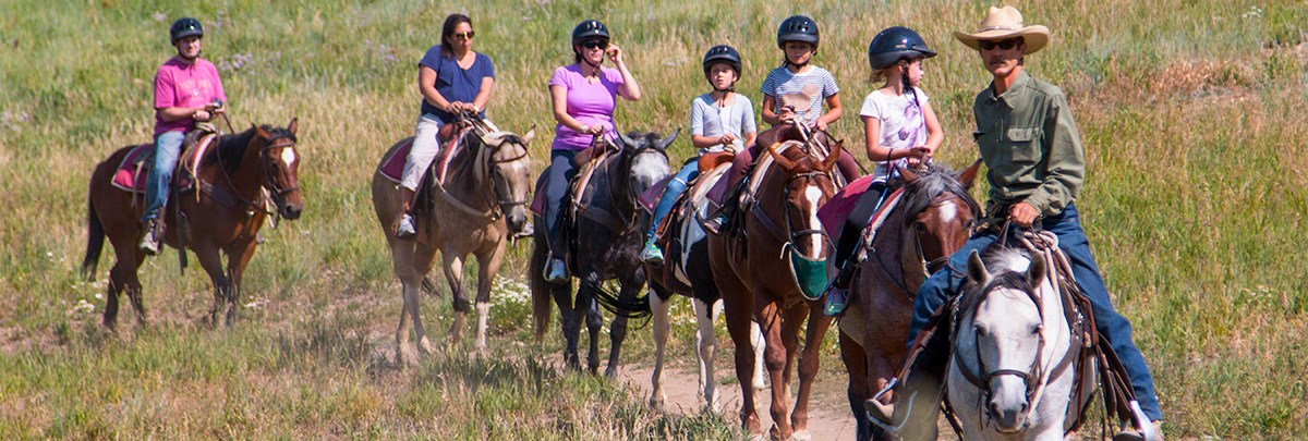 a horseback riding guide leading a group of people horseback riding
