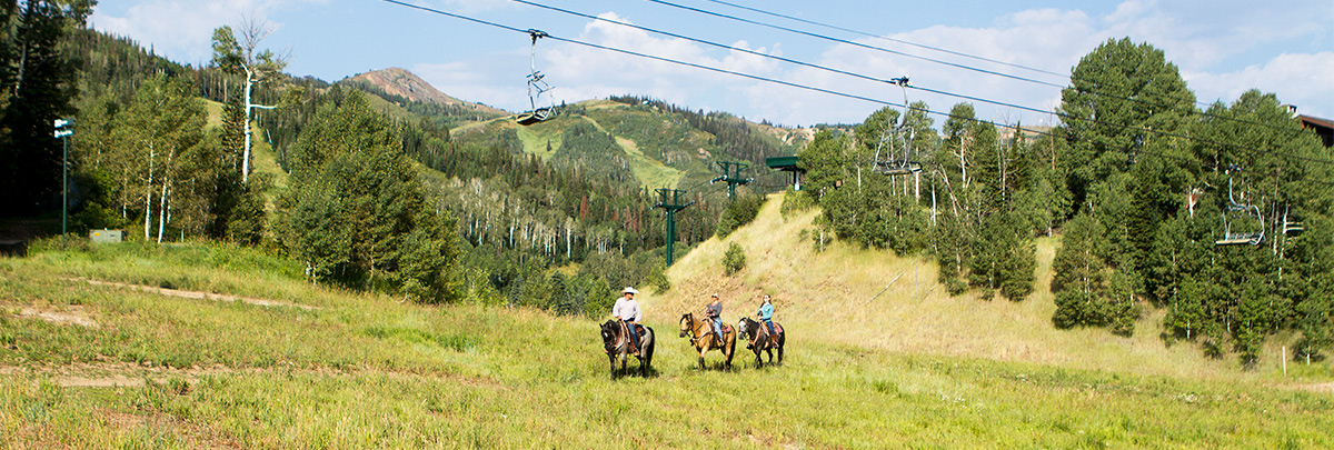 three people horseback riding underneath a chairlift with mountains in the background